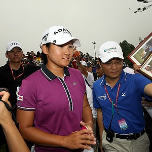 Yani Tseng is crowded by fans as she leaves the scoring tent after Friday's round. She is currently tied for third.