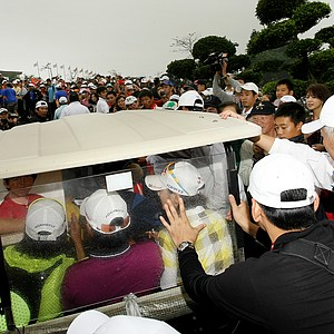 Yani Tseng, center, with her manager, Na Ya Hsu, left, and Na Yeon Choi, right, take cover in a golf cart trying to make their way to the clubhouse after Friday's round.