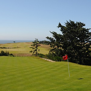 A view of the left side of the green, its clear how quickly the green falls off at No. 10. In the background, is the 17th hole of the Bandon Dunes course.