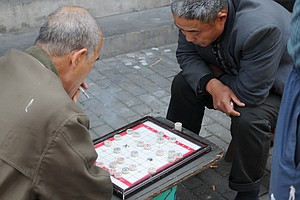 Two men playing Chinese chess in the streets of Shanghai.