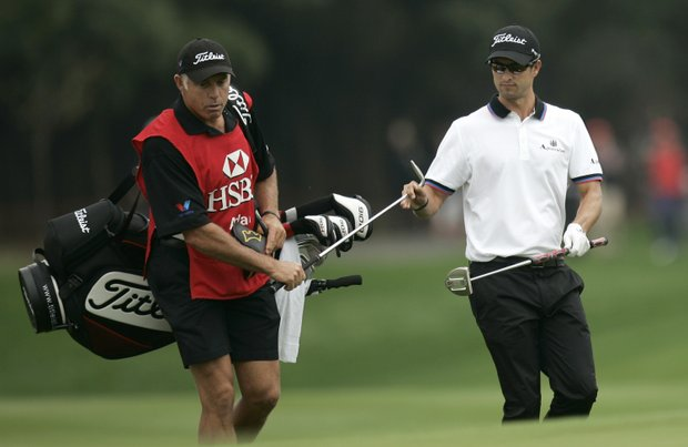 Adam Scott, right, passes his club to caddie Steve Williams on the 4th green during the final round of the HSBC Champions. Scott fired a 73 to finish eight shots back.