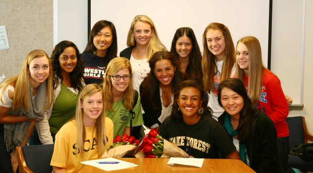 Mariana Sims (front right, at table) sits with her high school golf team after signing with Wake Forest.