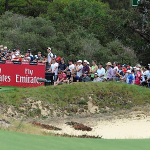 Tiger Woods is watched by a large gallery as he tees off on the 9th hole during the first round of the 2011 Australian Open.