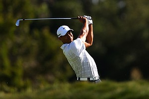 Tiger Woods hits his second shot on the 15th hole during day two of the 2011 Australian Open.