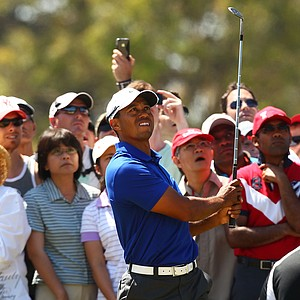Tiger Woods chips out of trouble on the eighth hole during day three of the 2011 Australian Open.
