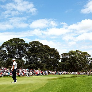 Tiger Woods waits to putt on the eighth hole as fans look on during day two of the 2011 Australian Open.