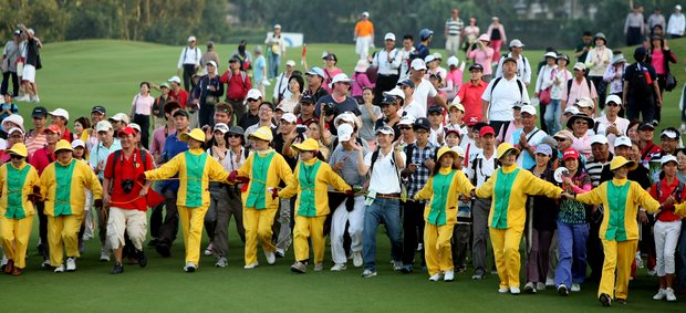 The Sunrise Golf and Country Club caddies try to keep the fans who rushed the fairway at No. 18 from going any further during the final round of the inaugural 2011 Sunrise LPGA Taiwan Championship.