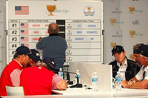 U.S. captain's assistants John Cook and Jay Haas (from left), U.S. Team captain Fred Couples, International Team captain's assistant Tim Clark and Frank Nobilo and International Team captain Greg Norman discuss the first day's foursomes matches.