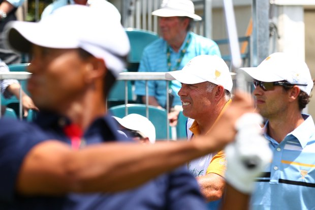 Tiger Woods of the U.S. hits his tee shot on the first hole as Adam Scott of the International team and caddie Steve Williams look on during the Day 1 Foursome matches at the 2011 Presidents Cup.