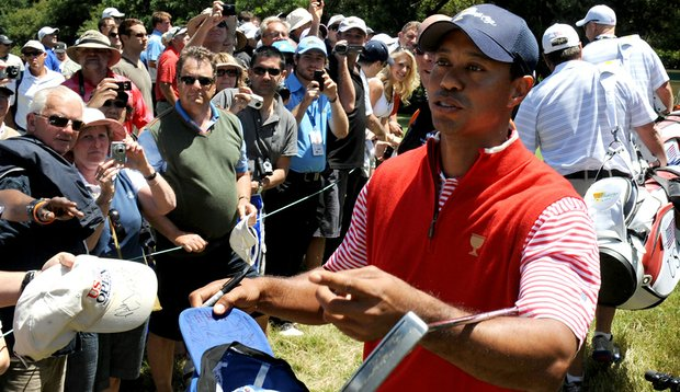 Tiger Woods signs autographs for fans at the Presidents Cup.