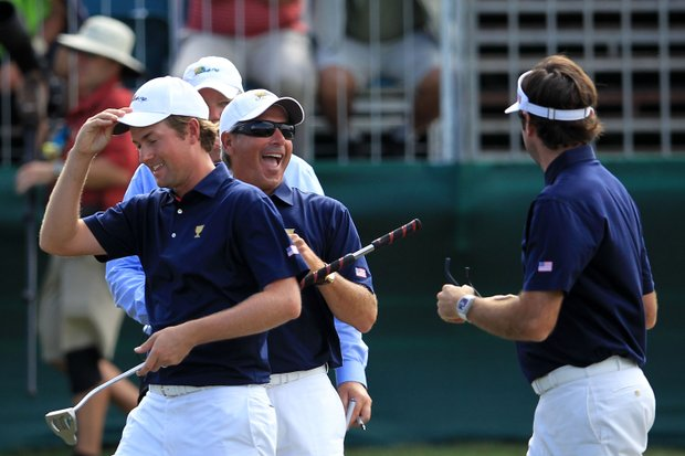 U.S. captain Fred Couples, center, celebrates with Webb Simpson, left and Bubba Watson of the U.S. team on the 16th green during the Day One Foursome matches.