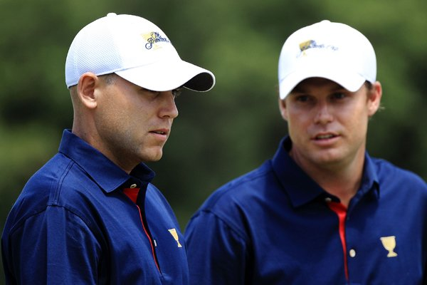 Bill Haas of the U.S. and teammate Nick Watney talk on the first green during the Day One Foursome matches.