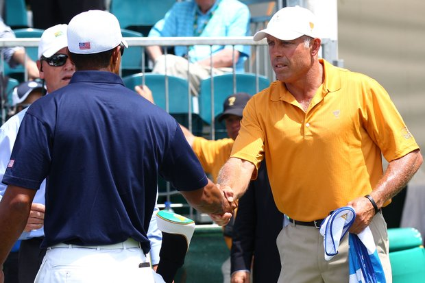 Tiger Woods of the U.S. and Steve Williams, caddie to Adam Scott, shake hands on the first tee during the Day 1 Foursome matches at the 2011 Presidents Cup