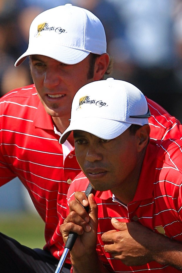 Dustin Johnson of the U.S. and teammate Tiger Woods line up a putt on the first green during the Day Two Four-Ball matches of the 2011 Presidents Cup.