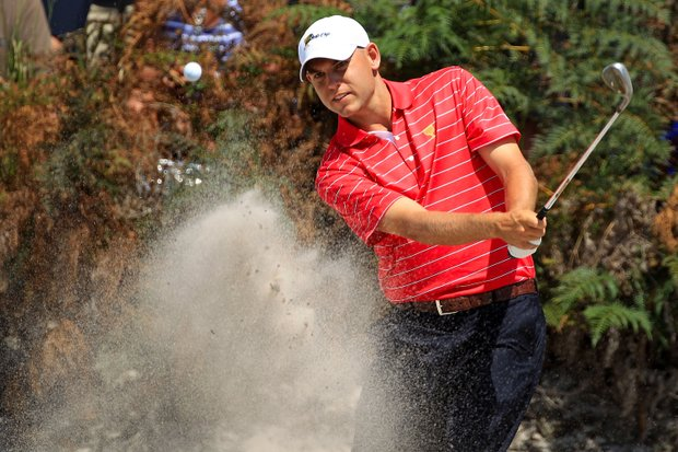 Bill Haas of the U.S. team hits from a bunker on the fourth hole during the Day Two Four-Ball matches of the 2011 Presidents Cup.