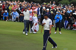Tiger Woods of the U.S. celebrates his birdie putt to win the match on the 16th hole alongside teammate Dustin Johnson during the Day Three morning foursome matches at the 2011 Presidents Cup.