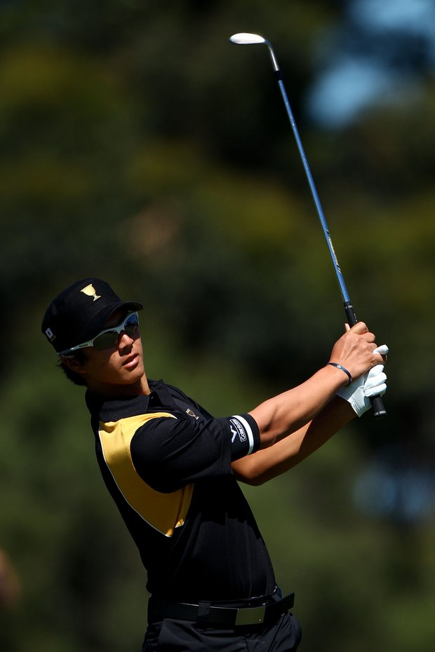 Ryo Ishikawa of the International team plays his second shot on the first hole during the Day Four singles matches of the 2011 Presidents Cup.