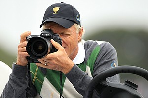 International captain Greg Norman takes a photo with a photographers camera on the seventh hole during the Day Three afternoon four-ball matches of the 2011 Presidents Cup.