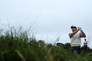 Steve Stricker of the U.S. hits his second shot on the ninth hole as his teammate Matt Kuchar looks on during the Day Three afternoon four-ball matches of the 2011 Presidents Cup.