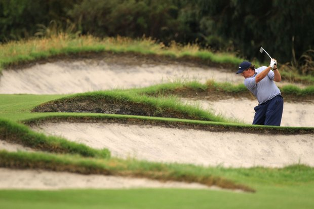 Phil Mickelson of the U.S. plays a bunker shot on the 15th hole during the Day Three morning foursome matches of the 2011 Presidents Cup.