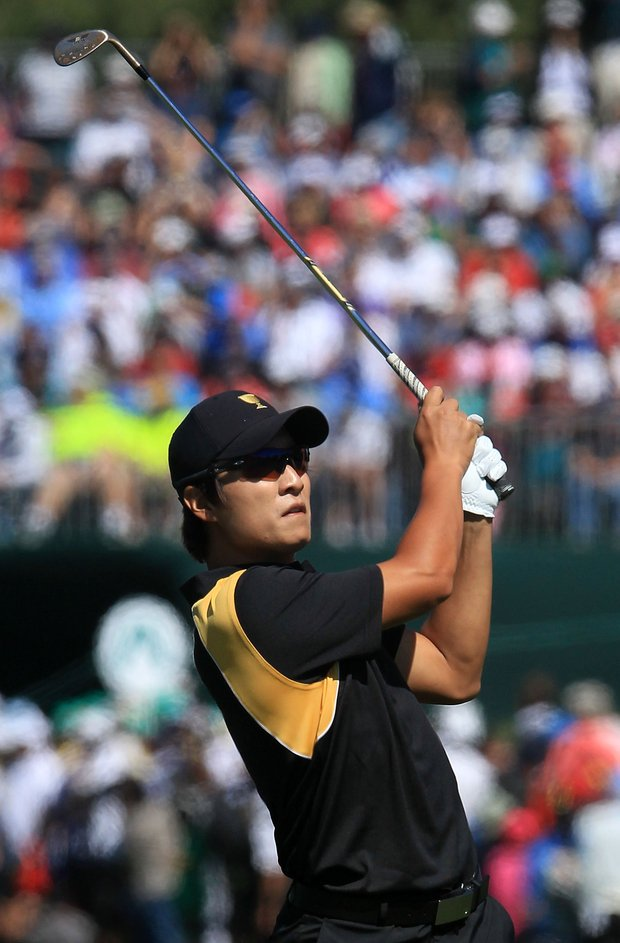 K.T. Kim of the International team hits his second shot on the first hole during the Day Four singles matches of the 2011 Presidents Cup.