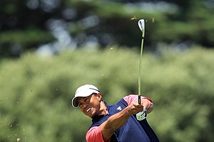 Tiger Woods of the U.S. hits an approach shot on the fourth hole during the Day Four singles matches of the 2011 Presidents Cup.