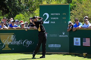 Charl Schwartzel of the International team hits his tee shot on the second hole as fans look on during the Day Four singles matches of the 2011 Presidents Cup.