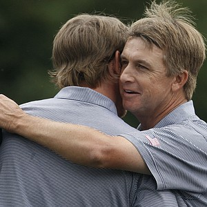 Hunter Mahan, left, is congratulated from his teammate David Toms on the 14th green after winning their foursomes match during the Presidents Cup.