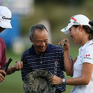 Family friends, Suk Moon, center, and Henry Kim, far left, congratulate Hee Young Park, during the final round of the CME Group Titleholders at Grand Cypress in Orlando, Fla.