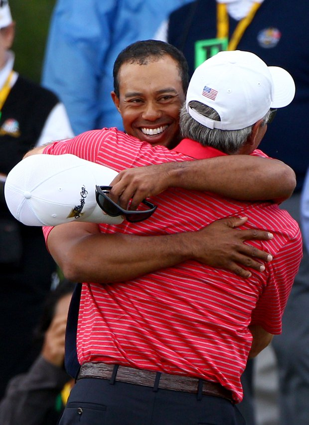 Tiger Woods of the U.S. embraces captain Fred Couples after winning his match on the 15th hole during the Day Four singles matches of the 2011 Presidents Cup.