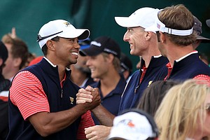 Tiger Woods of the U.S. shakes hands with teammate Jim Furyk after Woods clinched the Presidents Cup with a 4-and-3 victory over Aaron Baddeley.