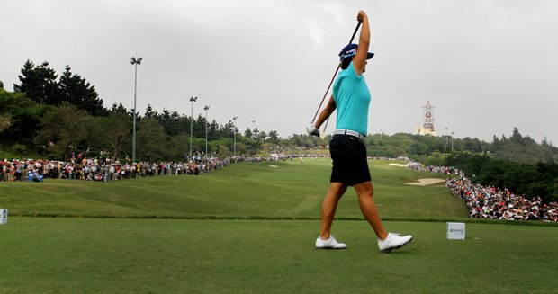 Yani Tseng stretches on the first tee prior to Thursday's round of the inaugural 2011 Sunrise LPGA Taiwan Championship. The crowd lined the whole fairway in anticipation of Tseng's first tee shot.