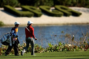 Jennie Lee and her caddie walk past the LPGA sign at No. 18 during the opening round of LPGA Qualifying School at LPGA International.