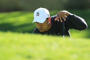 Tiger Woods lines up a putt on the fifth green during the first round of the Chevron World Challenge.