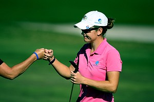 Julia Boland of Australia fist bumps her caddie, Cindy Harrington as she pulls out a par on Champions Course. Boland made the cut to compete in the final round.