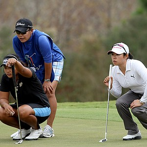 "Junthima ""Numa"" Gulyanamitta, left, with her sister/caddie Russy, at far right is Jennie Lee during the final round. Both Gulyanamitta and Lee secured LPGA membership for 2012."