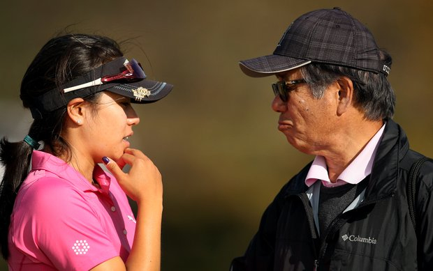 Stephanie Kono of UCLA talks with dad, Teruo Kono, while deciding whether to turn pro after finishing in the top 20 during the final round of LPGA Qualifying Tournament at LPGA International.