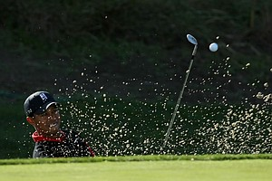Tiger Woods hits out of a bunker on the 12th hole during the final round of the Chevron World Challenge.