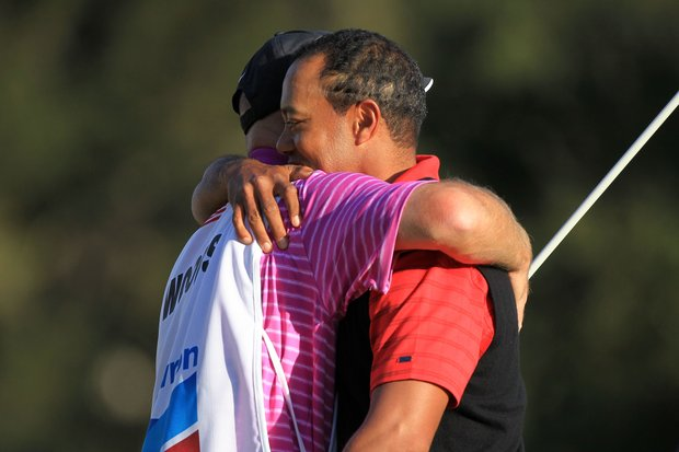 Tiger Woods hugs his caddie Joe Lacava on the 18th hole after winning the Chevron World Challenge.