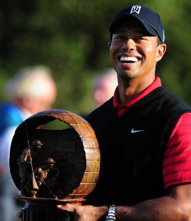 Tiger Woods is all smiles while holding the championship trophy at the 18th hole on the final day of the Chevron World Challenge.