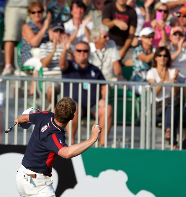 Luke Donald tosses a ball into the stands after finishing the fourth round at the Dubai World Golf Championship.