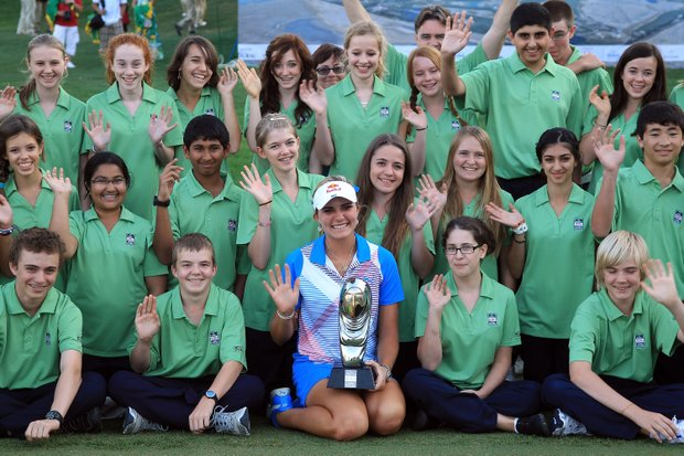 Lexi Thompson proudly holds the trophy after her four-shot victory with a group of Dubai schoolchildren who manned the scoreboards during the fourth round of the 2011 Omega Dubai Ladies Masters.