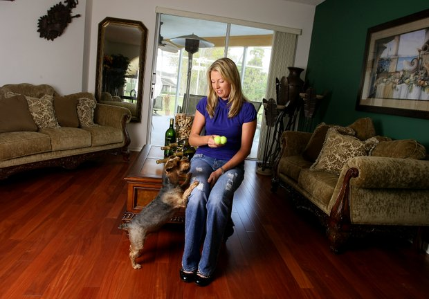 Beth Bauer, photographed in her home in 2009, toys around with her dog in her living room. Bauer is expecting her first child sometime in late 2011.