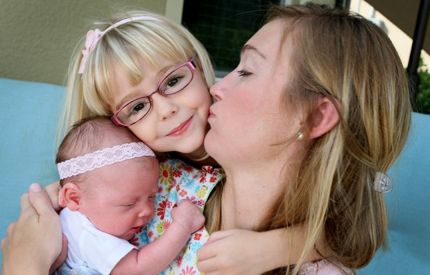 Catherine Tumbleson, formerly Cartwright plants a kiss on Maci during a recent photo shoot with Golfweek at her home in Bonita Springs, Fla. Baby Ella is at right.