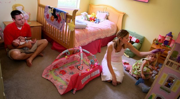 Catherine Tumbleson, center, in her daughter Maci's bedroom, playing with dolls. At left is her husband Jerrod and newest baby, Ella.