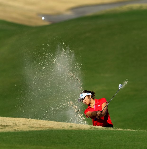 Alison Lee blasts out of the bunker at No. 18. She is currently tied for the lead with Samantha Wagner.