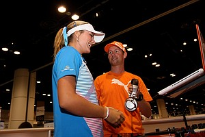 Lexi Thompson learns some tricks to being a disc jockey from D.J. Scotty at the Cobra Puma booth at the 2012 PGA Merchandise Show.