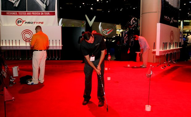 PGA Merchandise Show attendees try out putters at Odyssey's display during the opening of 2012 PGA Merchandise Show.