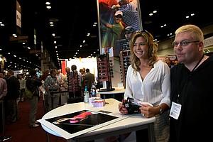 LPGA's Paula Creamer poses with Brian Strohmaier at the Sundog eyewear booth at the 2012 PGA Merchandise Show.