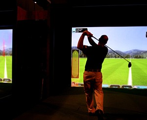 A show spectator test out the new Head Measurement Technology simulator from Foresight Sports during the final day at the 2012 PGA Merchandise Show.